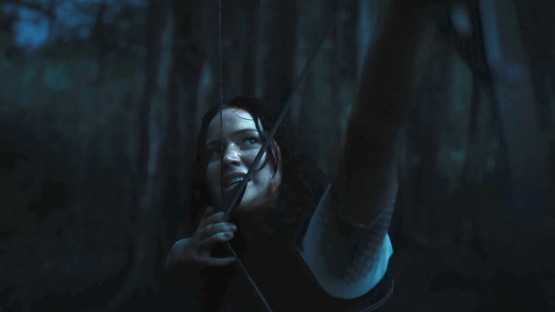 Katniss aims an arrow.