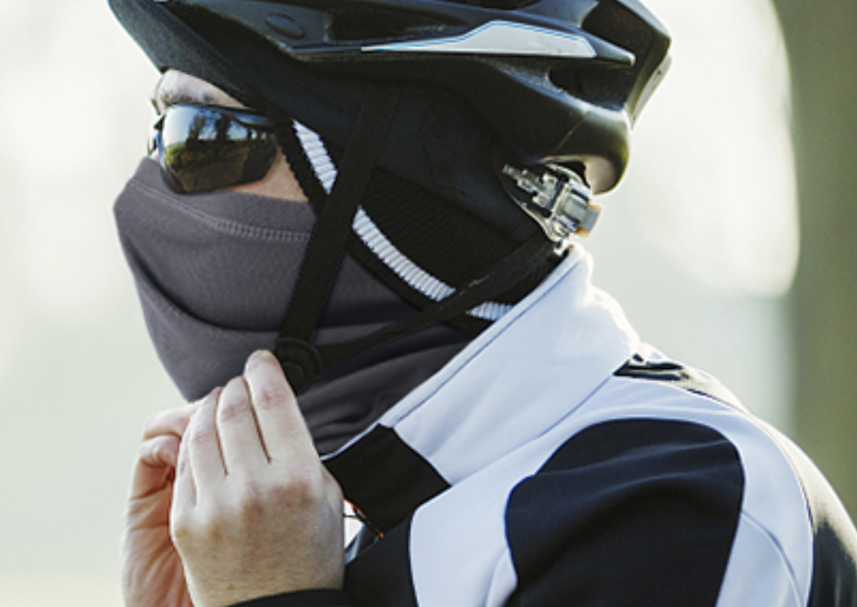 A model on a bike with a face covering on under their helmet