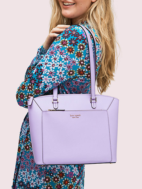 a model holding the lavender, square bag with a front pocket and thin leather straps