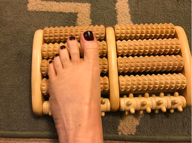 A reviewer's foot on the product, which has two columns of five rollers each, one of which has a different texture than the others