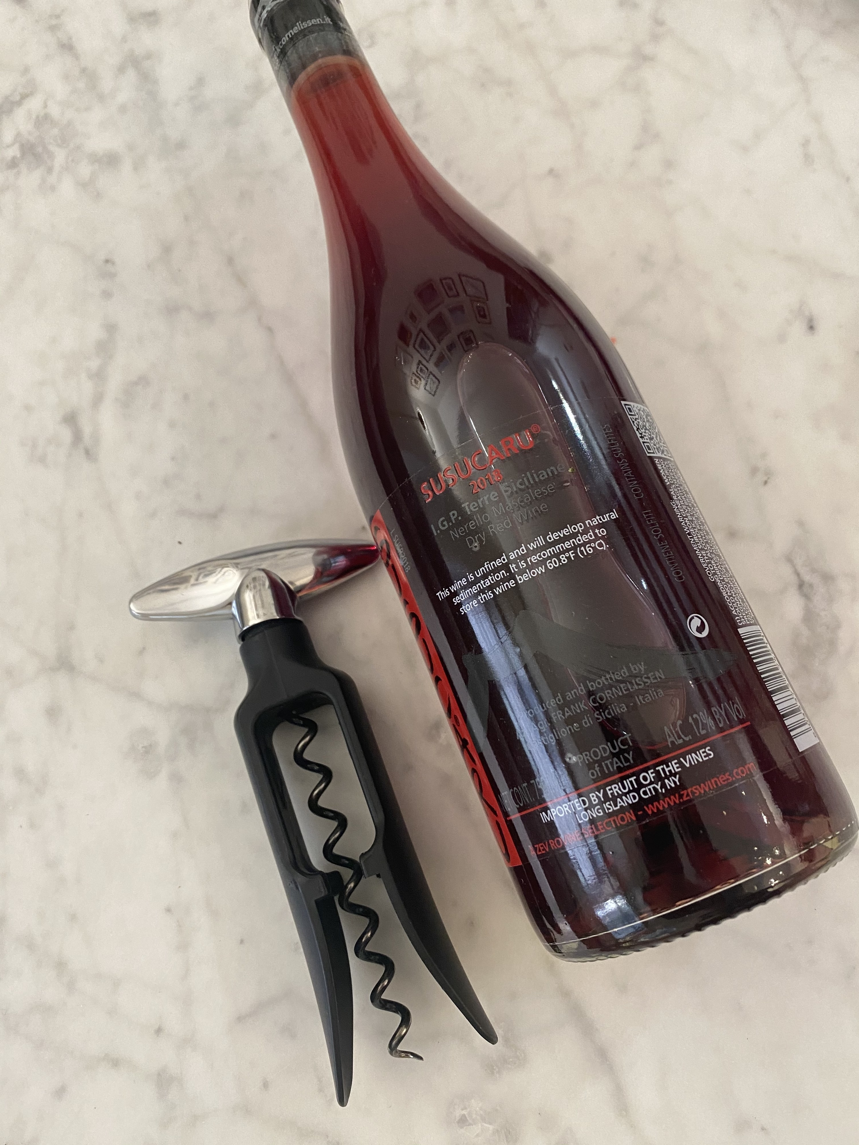 A bottle of red wine next to a corkscrew on a countertop.