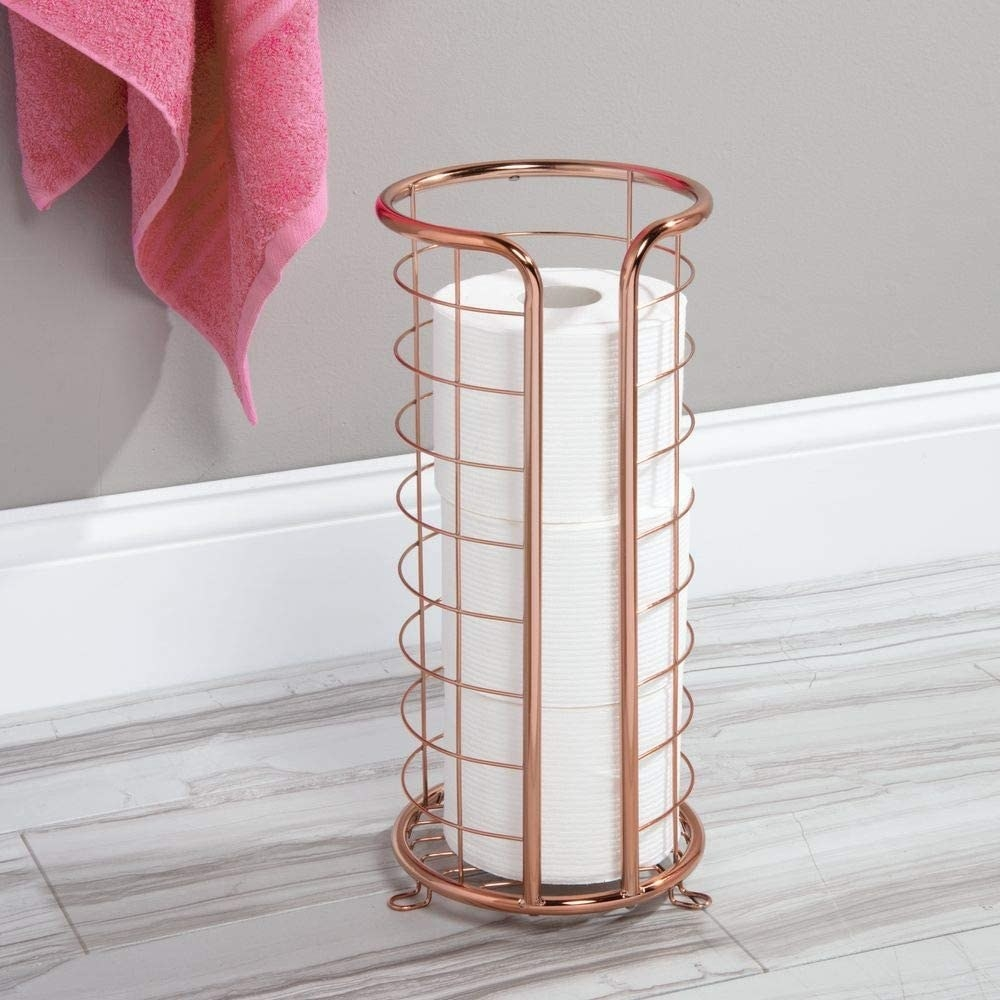 Metal toilet paper holder with three rolls in it