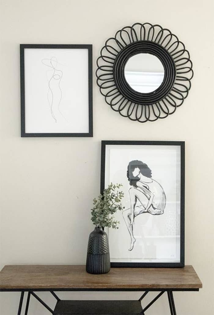 Line art print that looks like a model wearing a hat with a black frame as part of a gallery on a wall