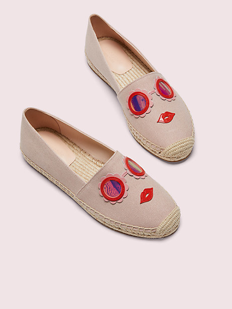 taupe slip-in espadrille shoes with flower-shaped mirrored glasses on the top above a pair of red lips