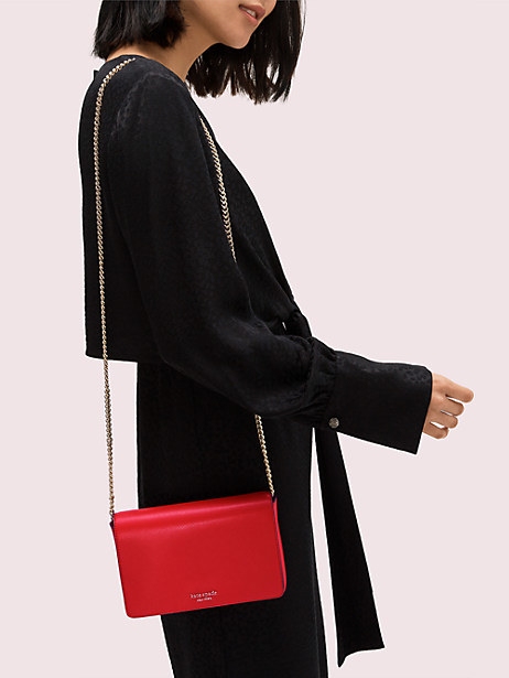 a model wearing the red, box-like, rectangular bag on their shoulder using the chain strap