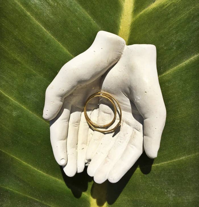 Small dish that looks like two hands coming together and holding a ring