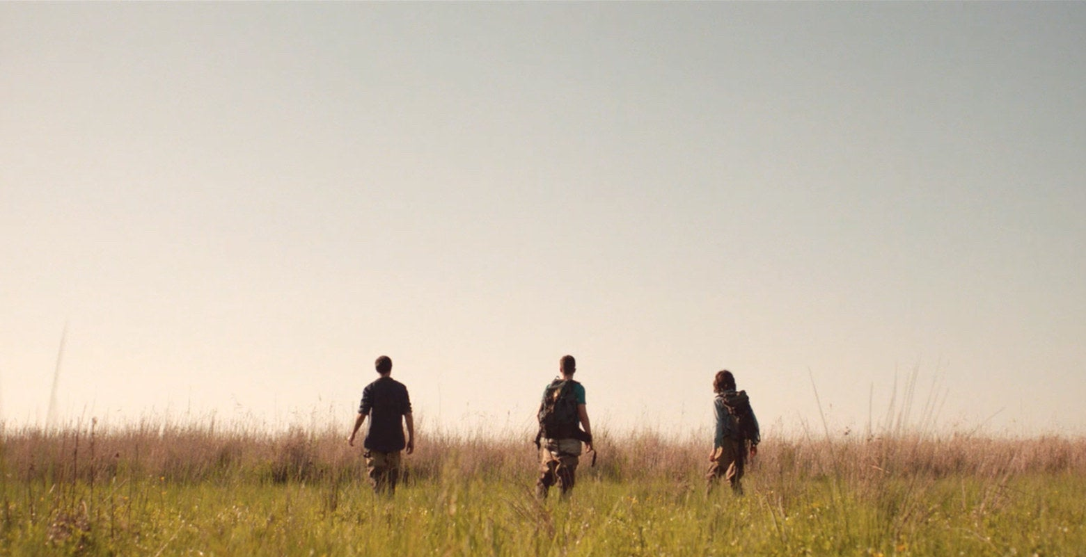 Three people walking inside of a marsh.