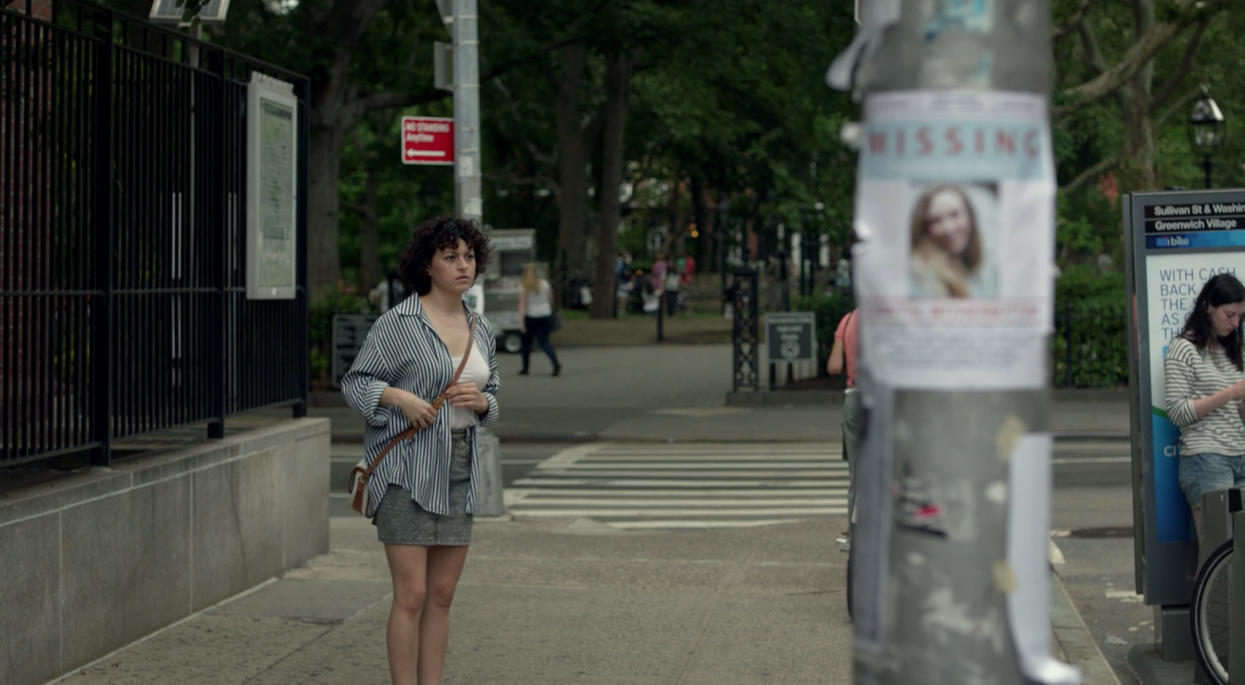 Screenshot of Alia standing in the streets near a missing persons poster