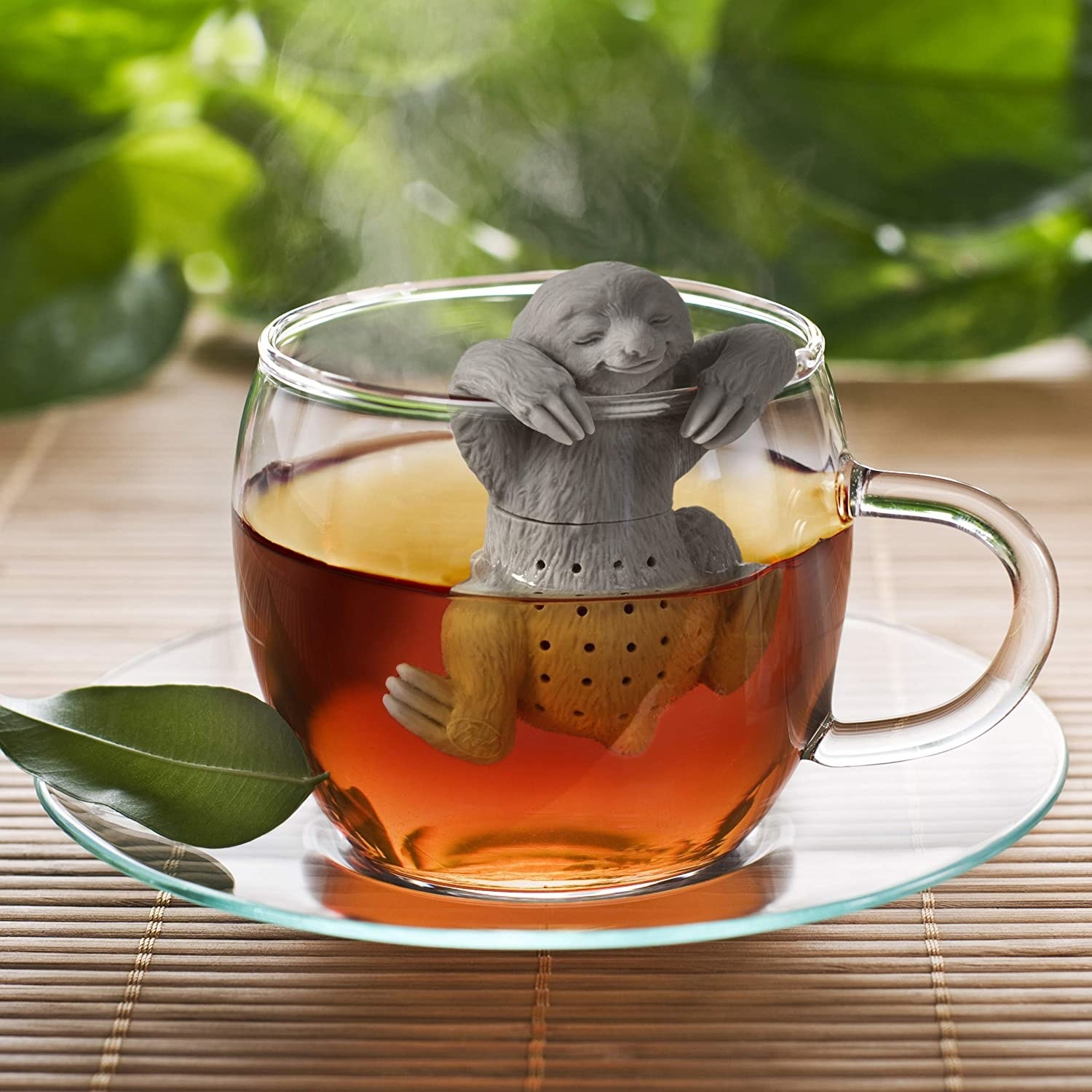 A sloth tea strainer sits in a coup of tea on a glass plate on a table