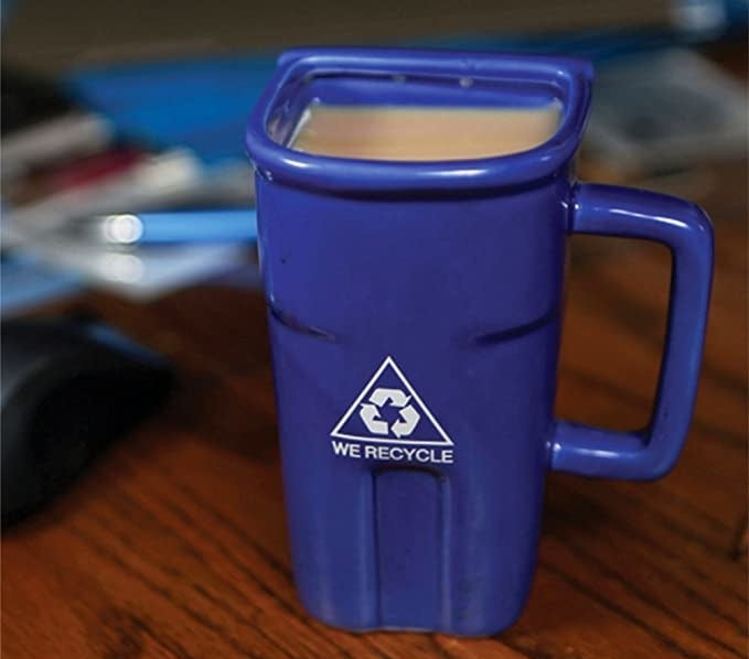 A mug that looks like a recycling bin is on a table and filled with liquid