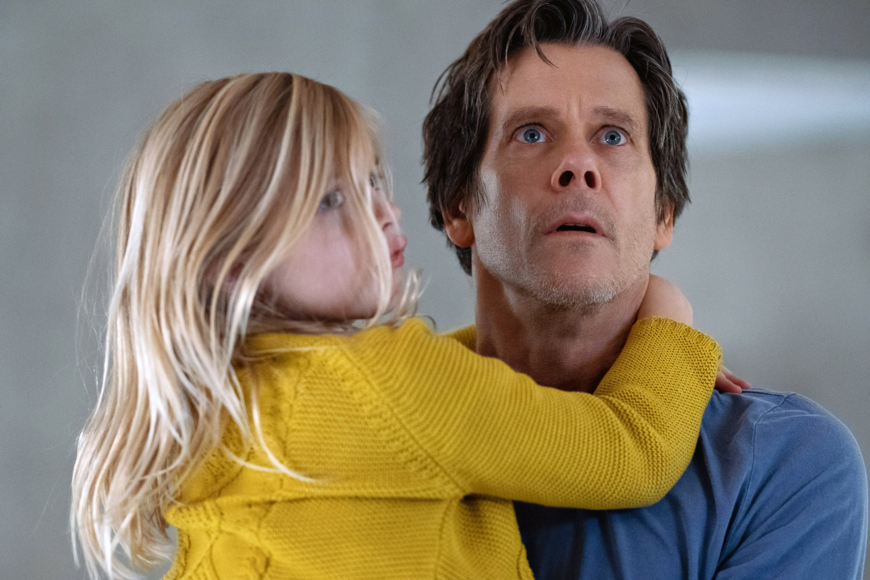 Kevin Bacon looks scared while holding his daughter.