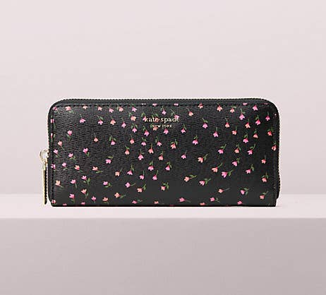 a black elongated rectangle wallet with a zip-around closure and tiny pink flowers all over it