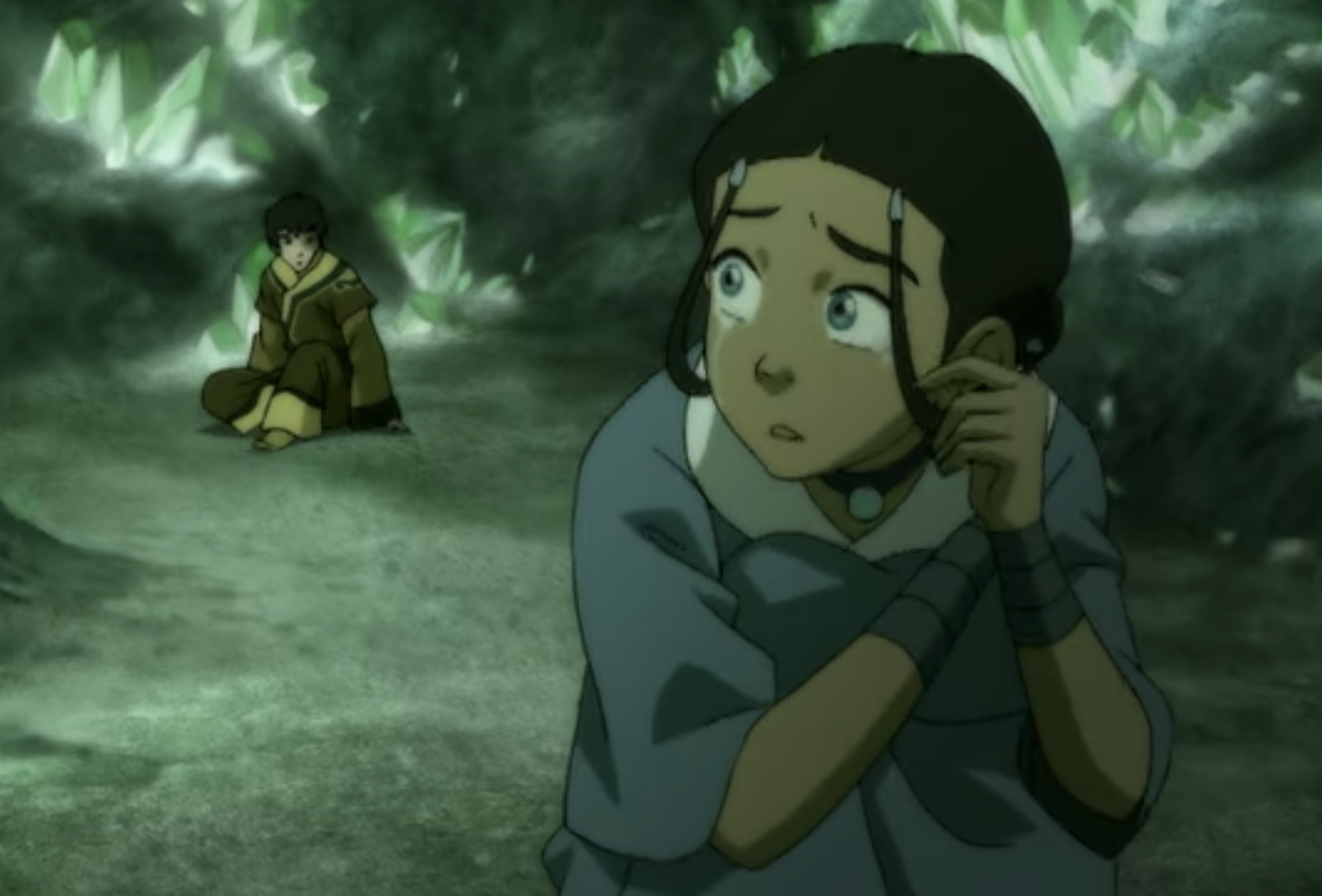 Katara crying while looking back at Zuko in a cave.