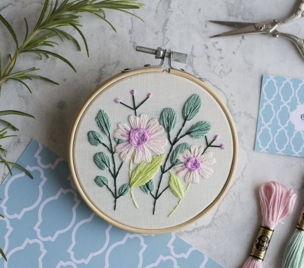 Embroidery hoop with two pink flowers and two green leaves emboridered on it
