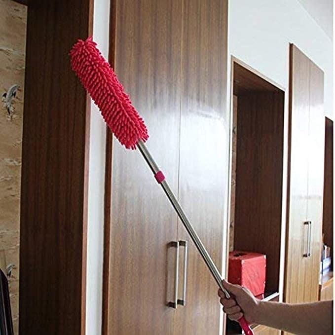 A hand using the red coloured brush to clean a cupboard.
