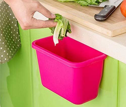 A hand putting some food bits into the trash can which is attached to the countertop.