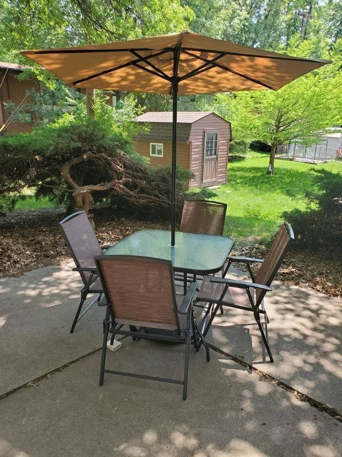 A reviewer photo of the set with four chairs, a table, and umbrella