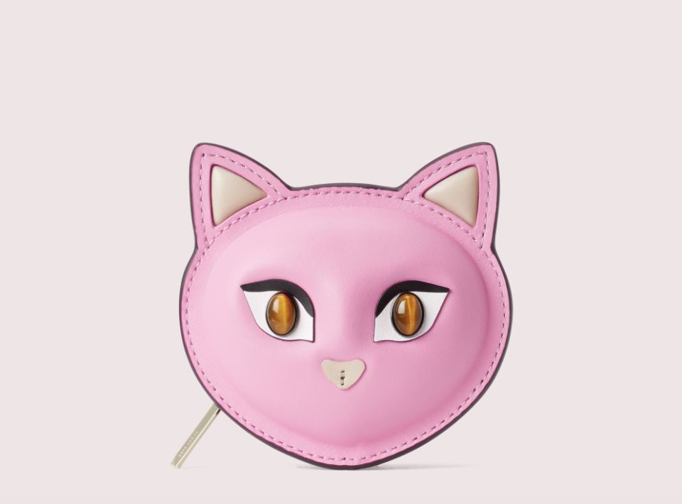 a pink coin purse shaped like a cat with brown beaded eyes and a tan heart-shaped nose
