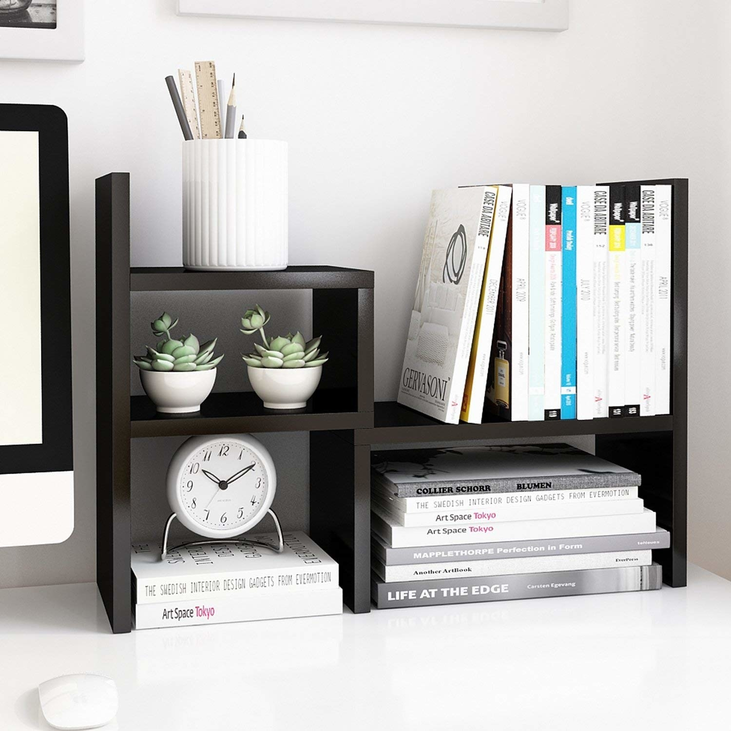 The asymmetric, rectangular-shelved unit in black, set up on a desk holding books, a pencil cup, succulents, and a clock
