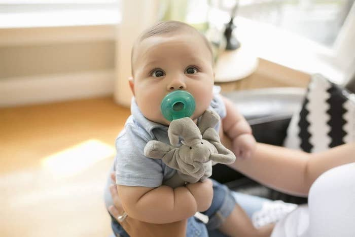 A baby with a pacifier in their mouth with a small stuffed animal hanging from it