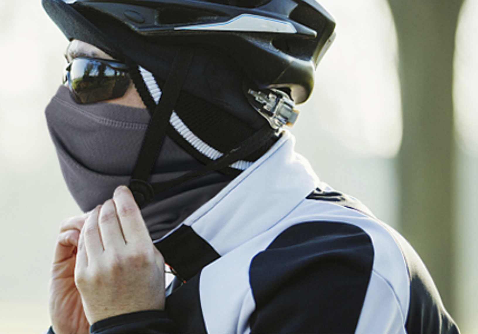 A model wearing the face covering under a helmet while riding a bike