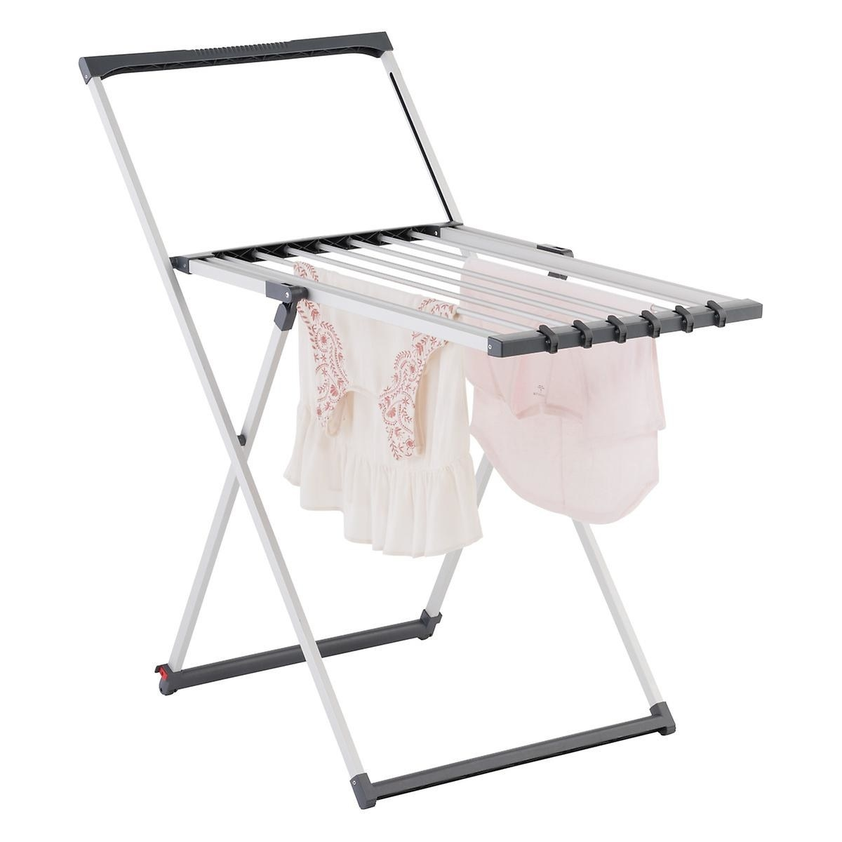 A metallic with gray accents drying rack with clothes hanging from it