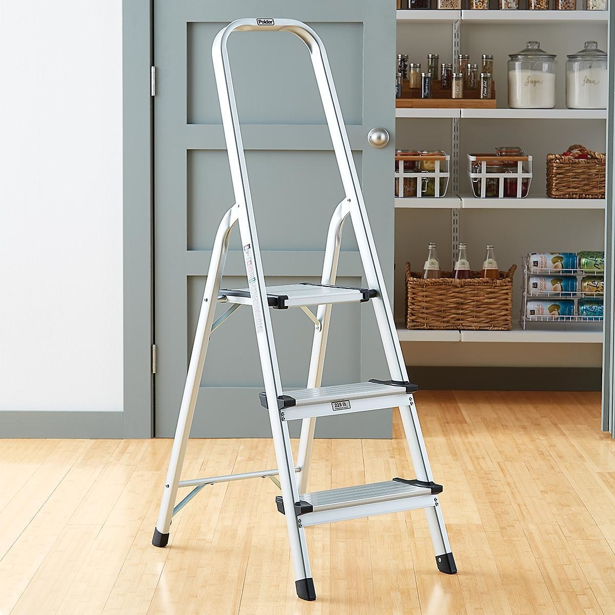 An unfolded metallic three-step ladder with black rubber edges and accents
