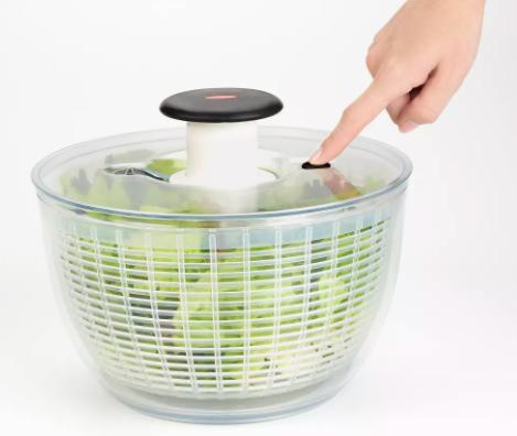Finger presses down on white OXO Salad Spinner