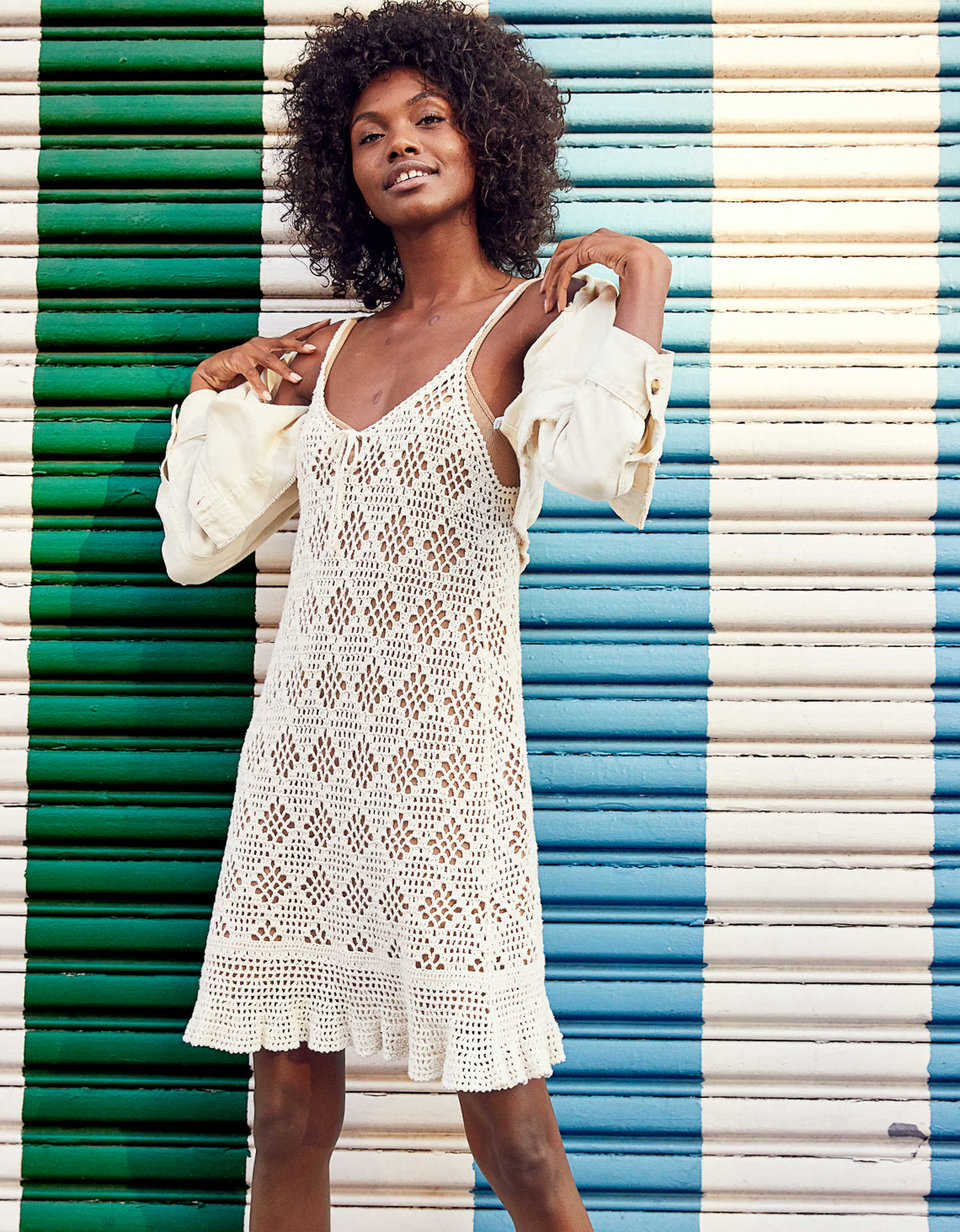 A model wears the Aerie crochet tank dress with a nude bralette and the Aerie empire cream cropped jacket
