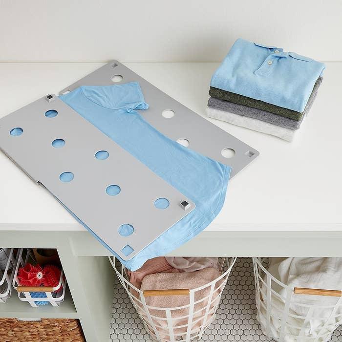A light gray laundry folder in the process of folding a light blue T-shirt