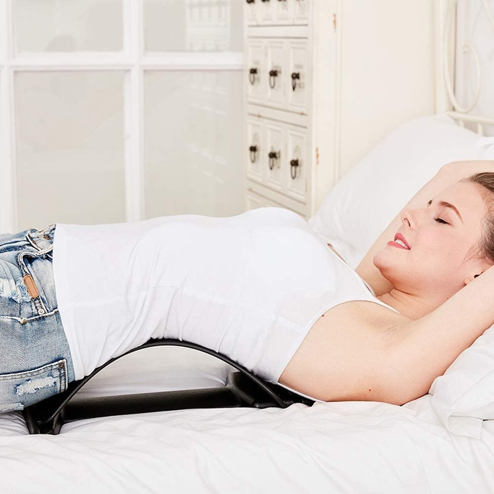 A model laying on top of the adjustable back stretcher. Their back is dramatically curved into a deep stretch, even while using it on a bed.