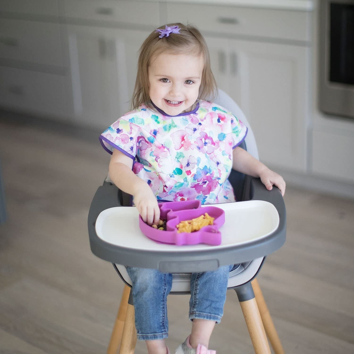 A small child sitting in a highchair eating They're wearing a bib with short sleeves