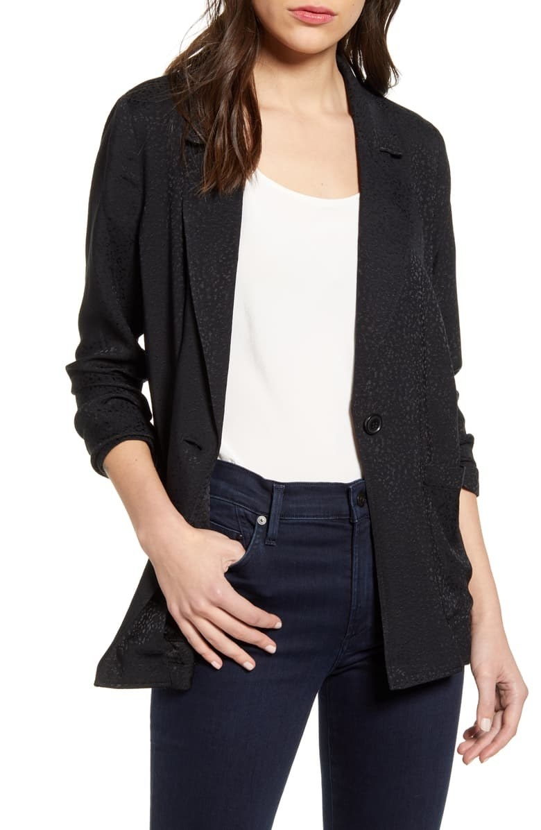 model wearing the subtly printed black blazer with one button, open and styled with a shirt and jeans