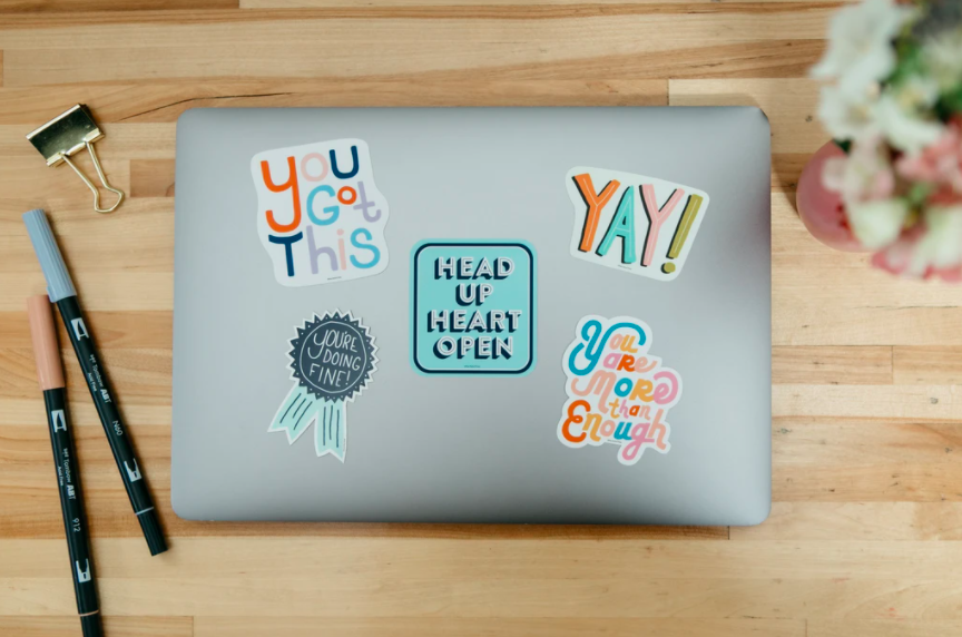 "The five stickers that say ""you got this"" ""yay"" ""head up heart open"" ""you are more than enough"" and ""you're doing fine!"" on a laptop"