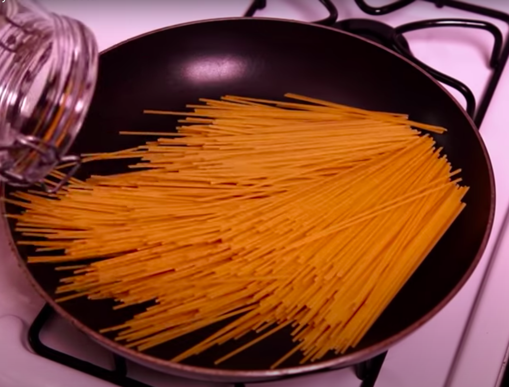Uncooked spaghetti in a pan.