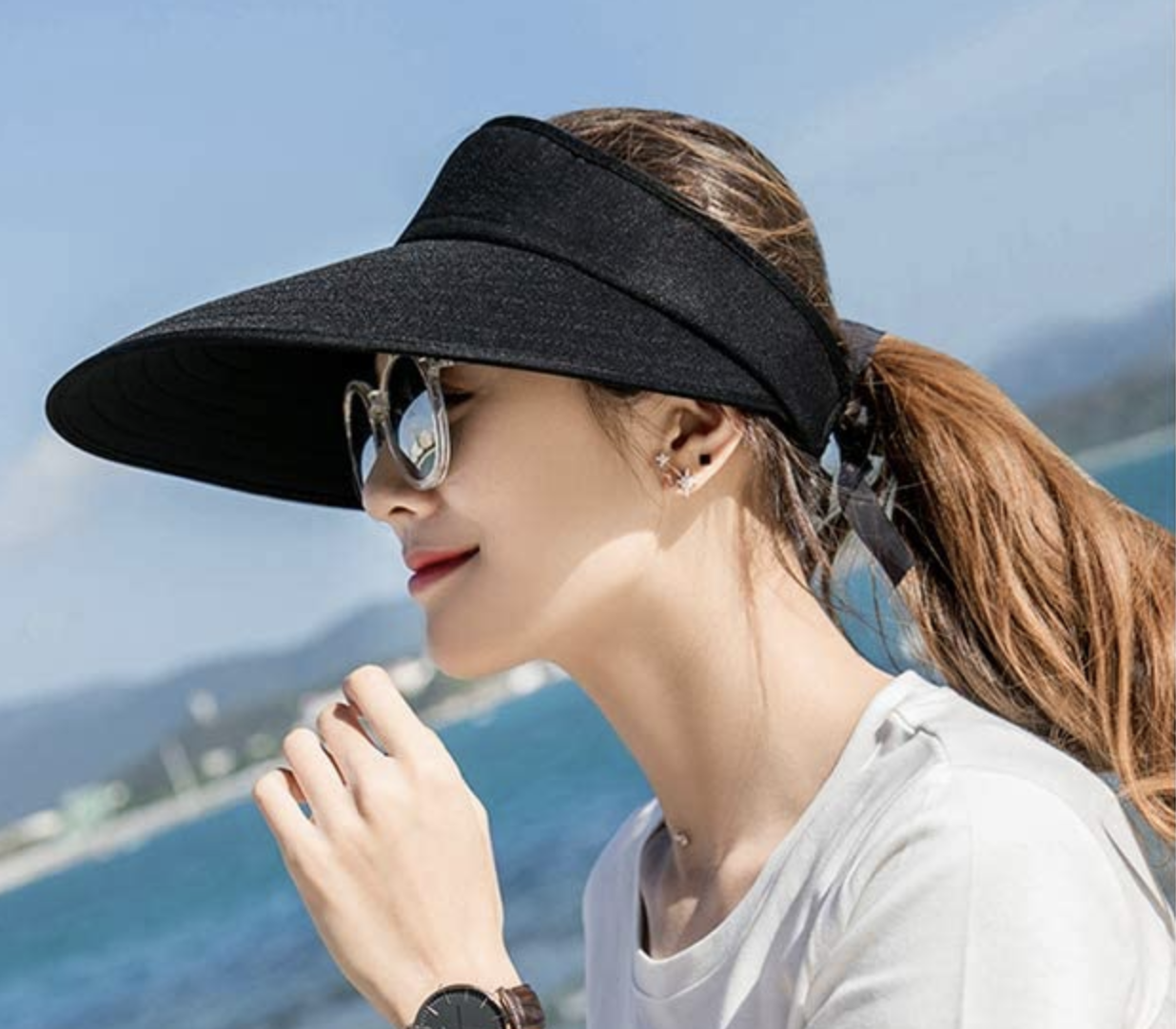 A model in a black visor with a long bill that shades their face