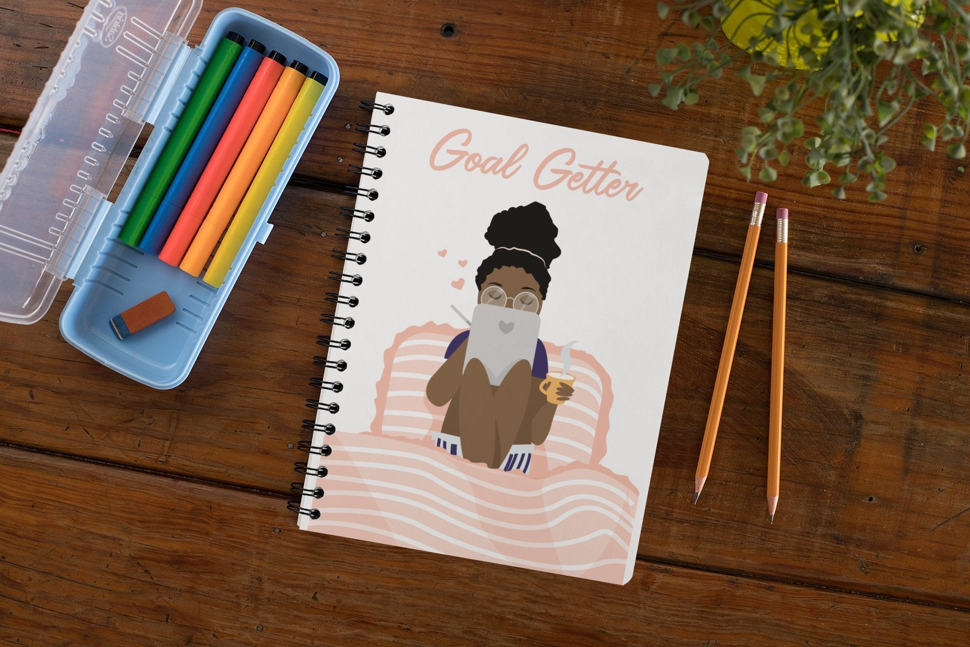 "a spiral notebook with ""goal getter"" written on it in light pink and a person with their hair up sitting in bed with a notebook and a cup of tea"