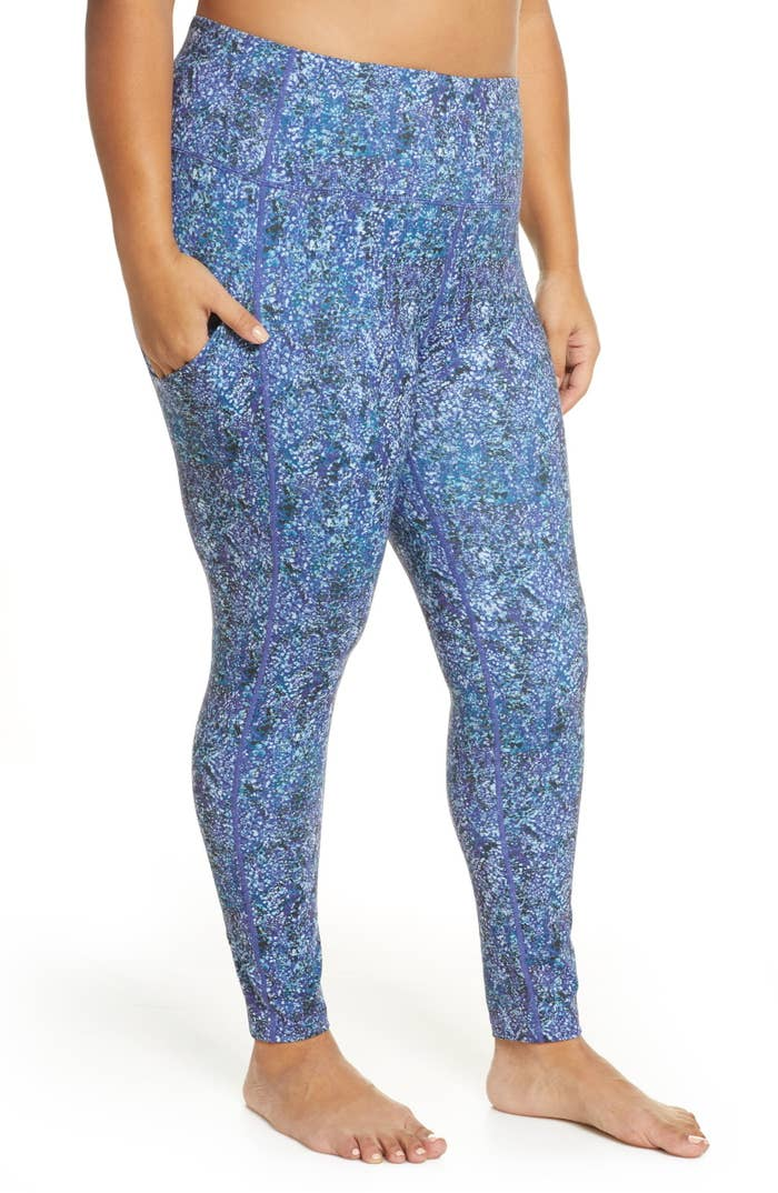 plus size model wearing high waist workout leggings in blue spotted snake print