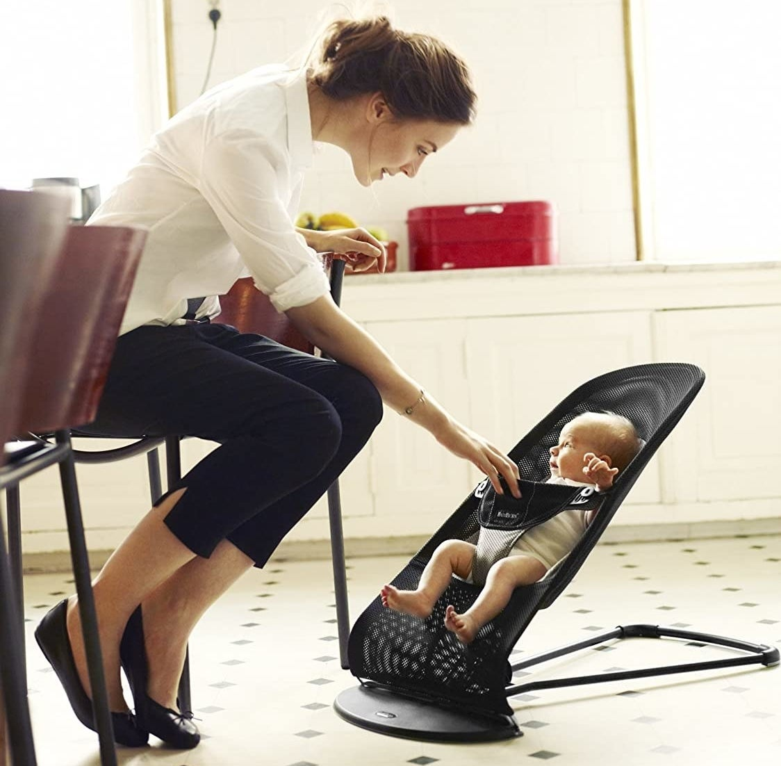 A person sitting on a chair and looking at their baby The baby is sitting upright in a mesh lounge seat on the floor
