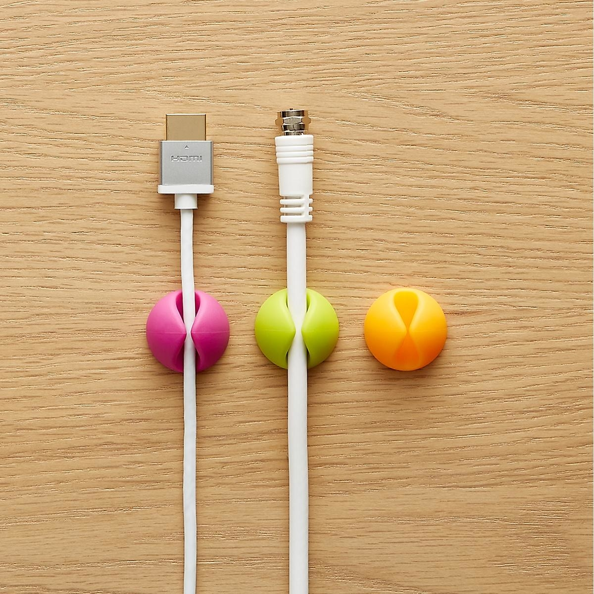 A set of three multi-colored clips in pink, lime green, and orange, two of which are securing cables