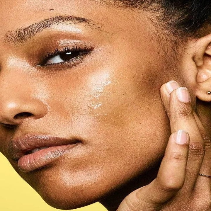 A model with dark skin rubbing the clear sunscreen onto their cheek with no visible residue