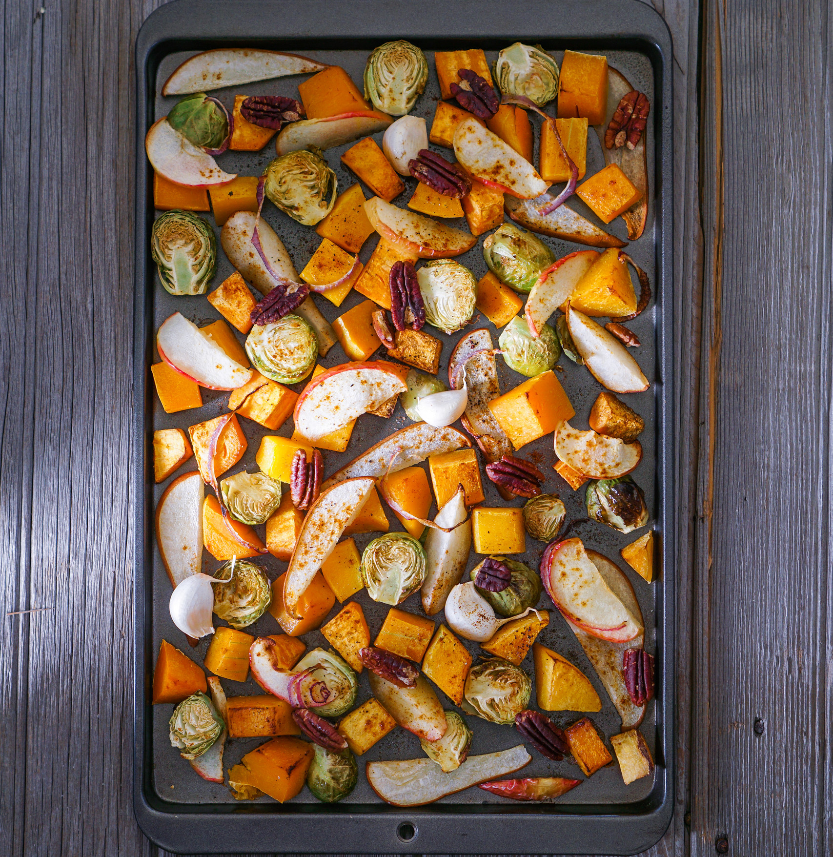 Roasted fruits and vegetables like butternut squash, Brussels sprouts, and sliced apples on a baking sheet.