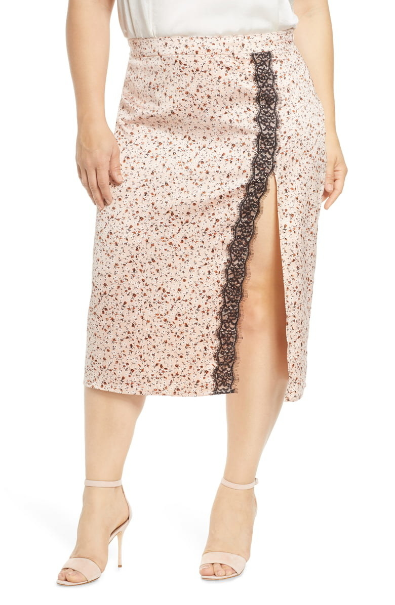 plus size model wearing the midi skirt in light pink with ditzy floral pattern, side slit on front in front of a leg, with black lace trim along the slit
