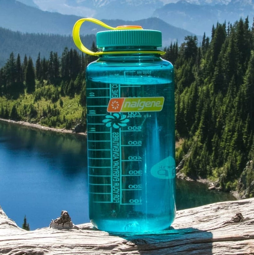 clear blue water bottle with green cap
