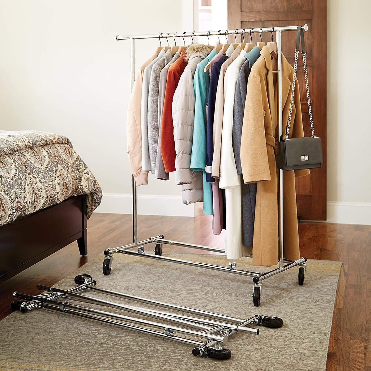 Two metal clothes racks, one fully-assembled filled with clothing, the other collapsed and on the floor