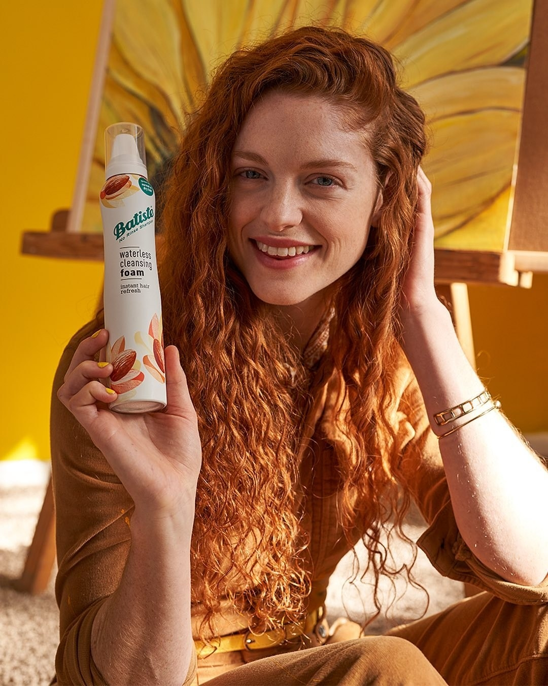 A person holds Batiste Waterless Cleansing foam and their hair is curly and refreshed looking