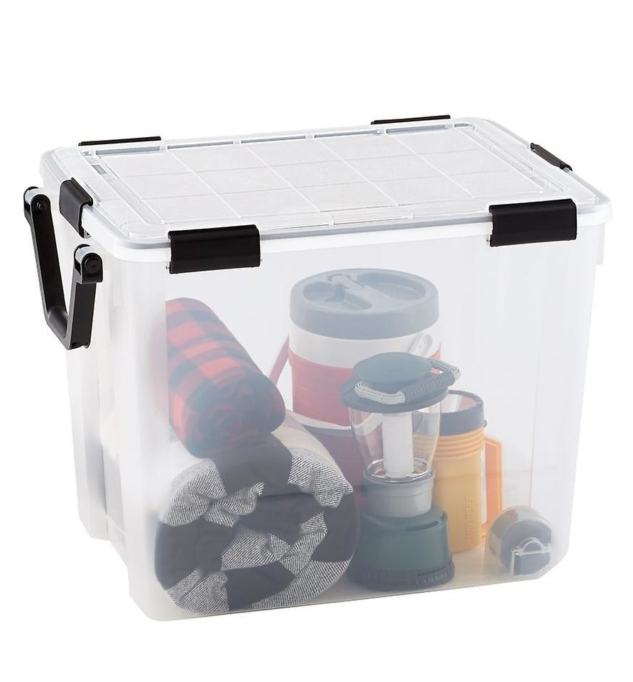 A clear plastic storage bin with a black handle filled with camping gear