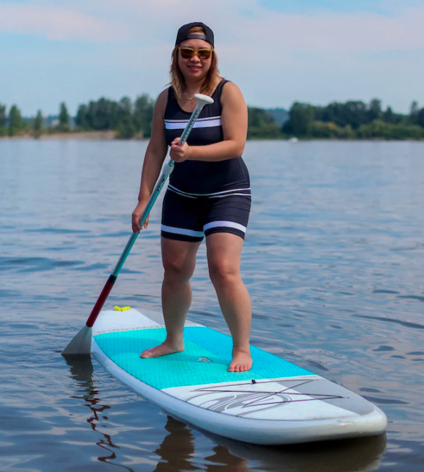 A model wearing the suit on a paddle board