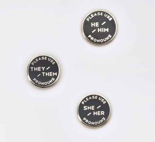 Three different pins with he/him, they/them, and she/her pronouns on them