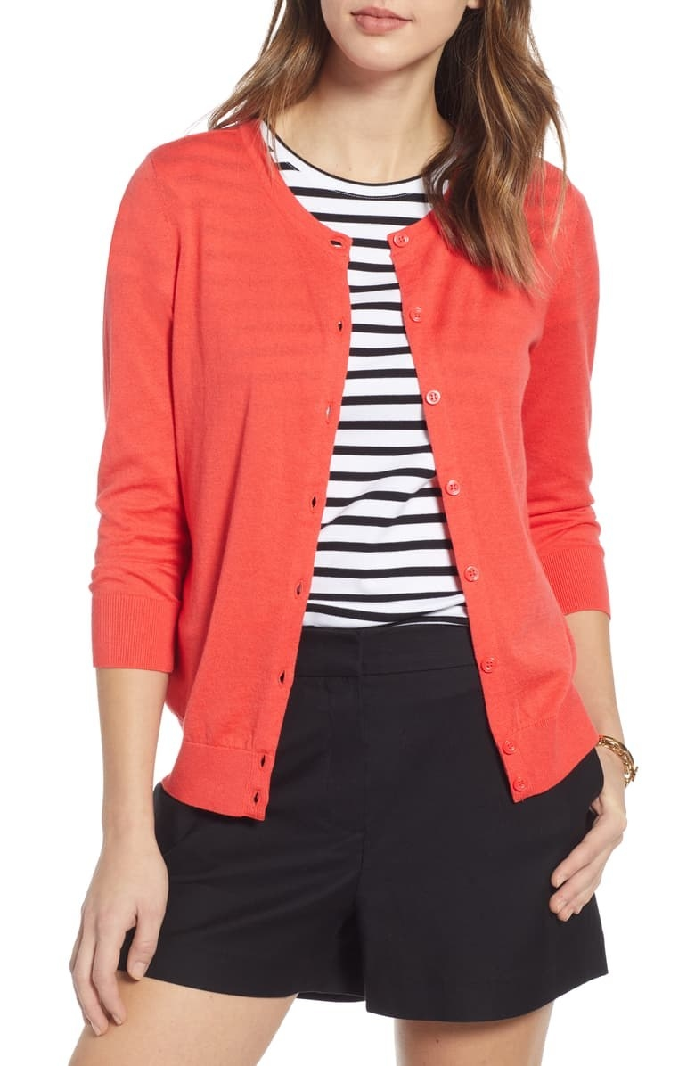 model wearing a bright right button down cardigan with a striped top, black shorts
